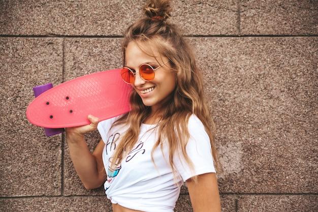 Schönes niedliches blondes teenager-modell ohne make-up in weißen hipster-kleidern des sommers mit rosa penny-skateboard, das nahe wand auf der straße aufwirft