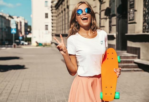 Schönes niedliches lächelndes blondes teenager-modell in sommer-hipster-kleidung mit orangefarbenem penny-skateboard-aufstellen. friedenszeichen zeigen