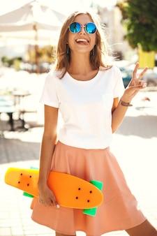 Schönes niedliches lächelndes blondes teenager-modell in sommer-hipster-kleidung mit orangefarbenem penny-skateboard-aufstellen. zeige zunge und friedenszeichen