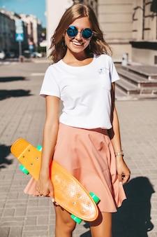 Schönes niedliches lächelndes blondes teenager-modell in sommer-hipster-kleidung mit orangefarbenem penny-skateboard, das aufwirft