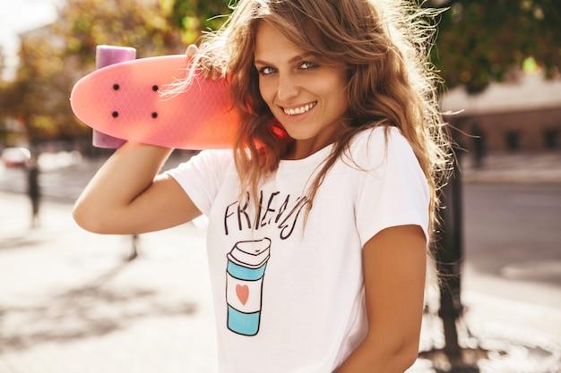 Schönes niedliches lächelndes blondes teenagermodell ohne make-up in weißen hipster-kleidern des sommers mit rosa penny-skateboard, das auf dem straßenhintergrund aufwirft