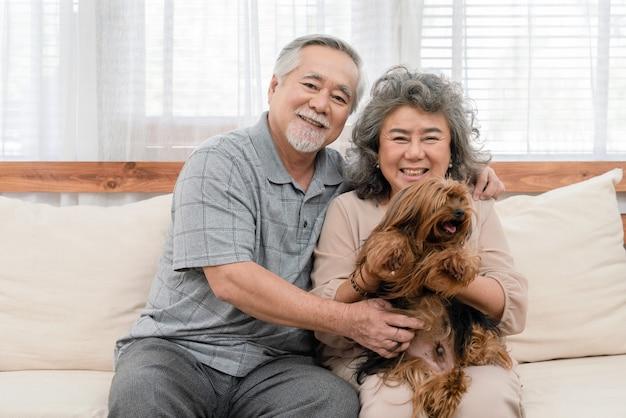 Schönes paar asiatischer älterer menschen mit ihrem hund, der zu hause auf dem sofa sitzt
