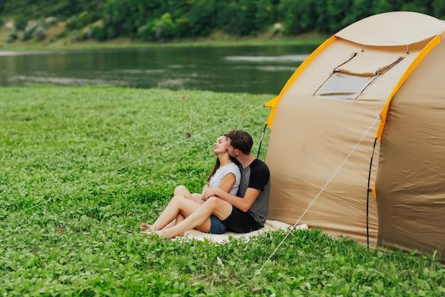 Schönes paar auf dem campingplatz mit zelt in der nähe des flusses.