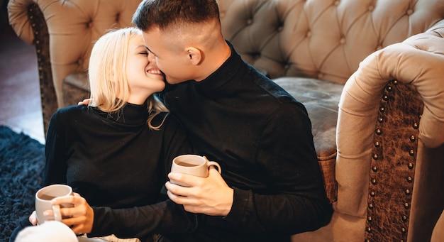Schönes paar, das auf dem boden im wohnzimmer sitzt und zusammen einen tee trinkt, während es sich neben dem sofa küsst und umarmt