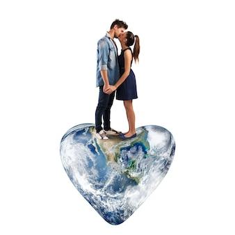 Schönes paar, das auf einer herzförmigen welt küsst