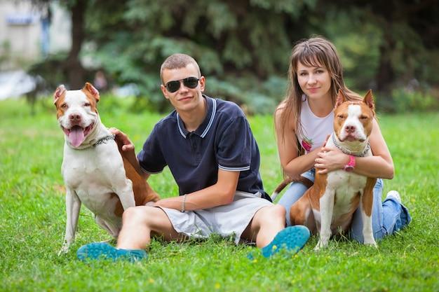 Schönes paar, das auf gras mit hunden sitzt