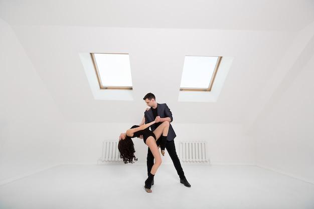 Schönes paar, das bachata auf weißem raum tanzt