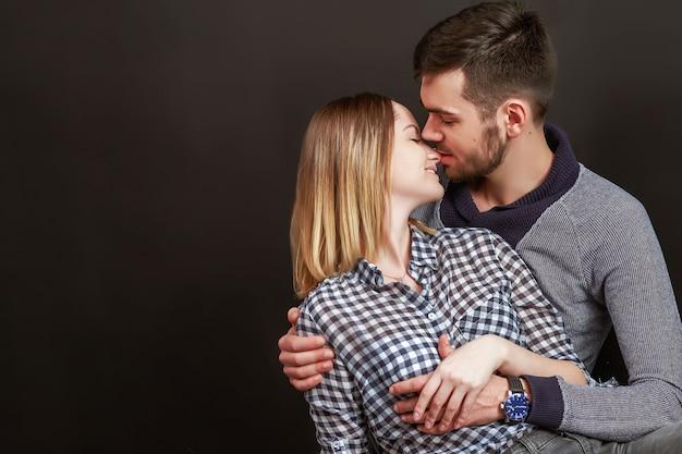 Schönes paar, das beim sitzen gegen schwarzen hintergrund küsst. studioaufnahme