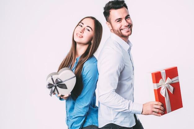 Schönes paar, das geschenke hält und kamera betrachtet