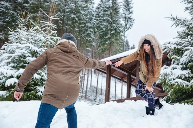 Schönes paar, das hände greift und sich beim wandern in den bergen im winter hilft helping