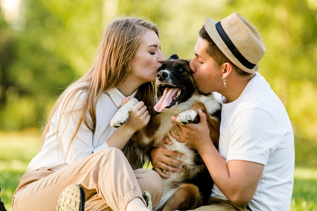 Schönes paar, das ihren lächelnden hund im park küsst