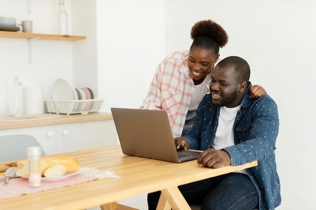 Schönes paar, das ihren laptop betrachtet