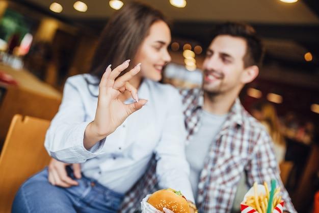 Schönes paar, das im fast food sitzt und okey zeigt