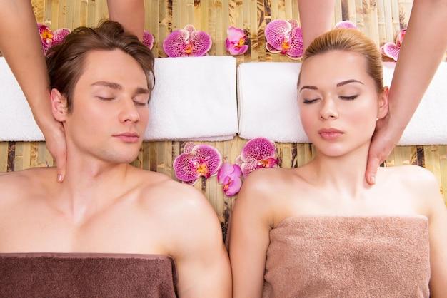 Schönes paar, das in einem spa-salon liegt, der kopfmassage zusammen genießt.
