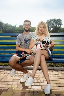 Schönes paar, das mit französischer bulldogge auf bank im park sitzt