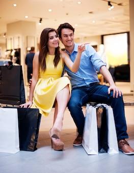 Schönes paar, das nach luxuseinkauf ruht