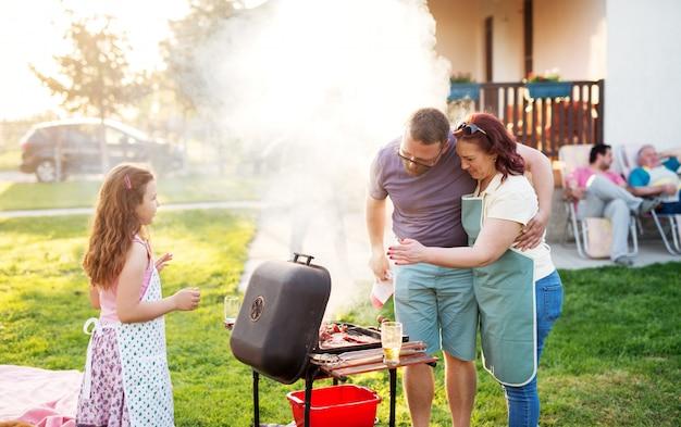 Schönes paar, das nahe steht und sich vor dem grill umarmt, während ihre tochter sie ansieht.