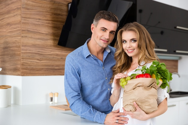 Schönes paar, das papierpaket mit essen hält, das auf der küche steht