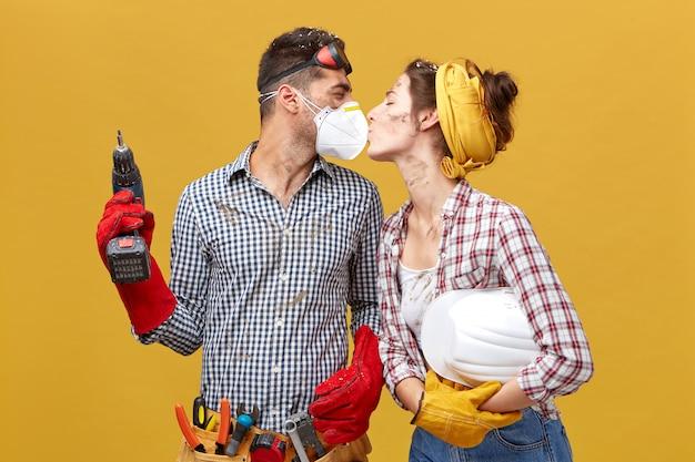 Schönes paar, das reparatur ihres hauses tut, das zusammen arbeitet und minute der entspannung hat, die leidenschaftlich küsst. junger baumeister männlich in der maske mit bohrmaschine, die mit liebe seine freundin ansieht