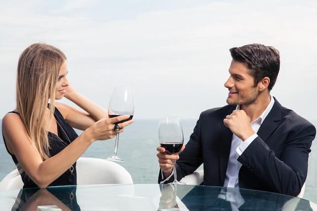 Schönes paar, das rotwein im straßencafé trinkt
