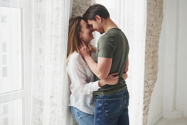 Schönes paar, das sich am fenster ihres neuen zuhauses küsst und genießt.