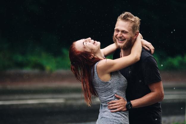 Schönes paar, das sich draußen im regen umarmt