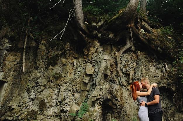 Schönes paar, das sich in der nähe eines gebirgsflusses umarmt