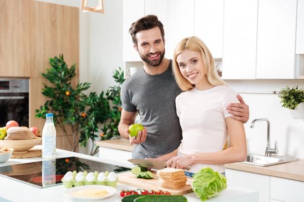 Schönes paar, das sich in ihrer küche umarmt