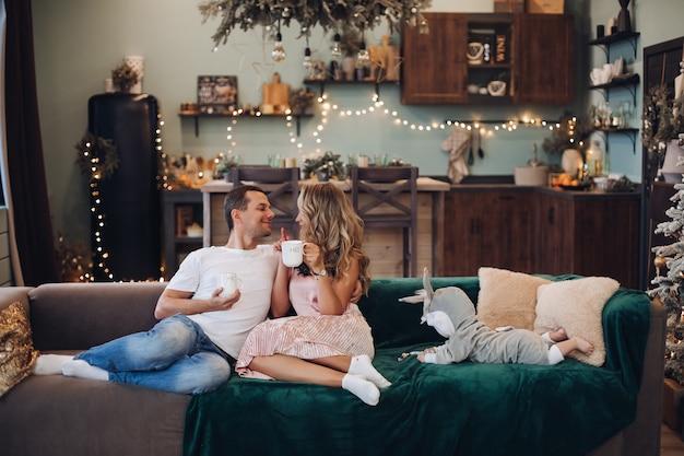 Schönes paar, das tee auf einer couch trinkt, während süßes baby neben ihnen kriecht. neujahrskonzept