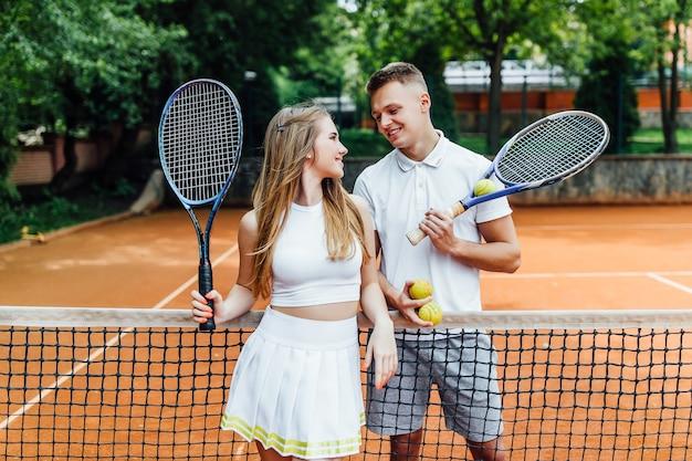 Schönes paar, das tennis spielt und glücklich zueinander schaut.