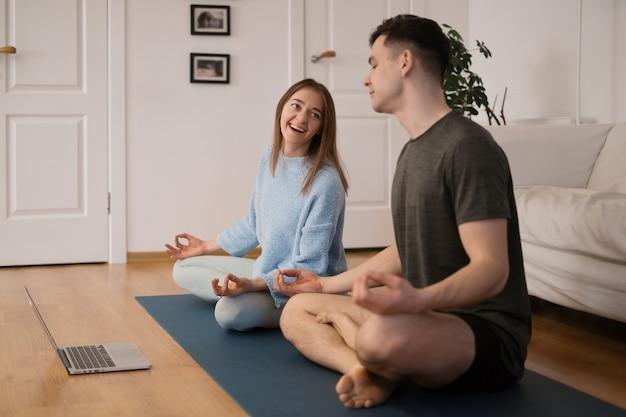 Schönes paar, das yoga zusammen zu hause mit einem laptop praktiziert, der online-yoga-kurse nimmt