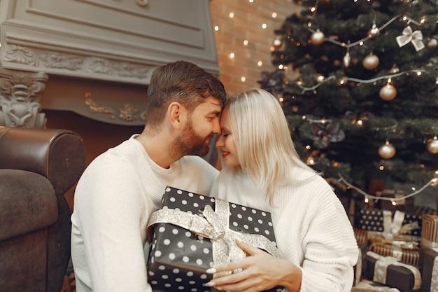 Schönes paar, das zu hause nahe weihnachtsbaum sitzt