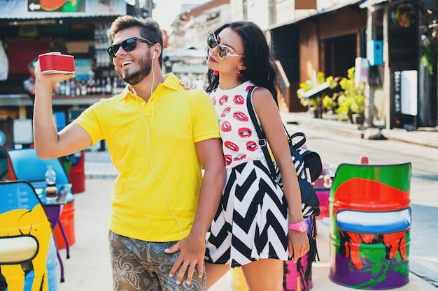 Schönes paar des jungen stilvollen hipsters, das im bunten café sitzt, flirtet, mode-outfit, trendiges outfit, sonnenbrille, tropischer urlaub, urlaubsromantik, honigmond, lächelt, glücklich, musik hört
