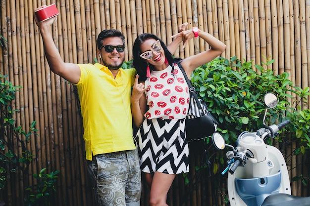 Schönes paar des jungen stilvollen hipsters in den sommerferien in thailand, flirtend, modetrend-outfit, sonnenbrille, tropischer urlaub, urlaubsromantik, lächeln, glücklich, musik hören, party, tanzen