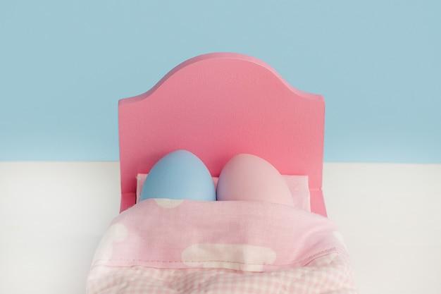 Schönes paar eier schlafen in einer umarmung im bett. händchenhalten. osterferienkonzept mit niedlichen eiern mit lustigen gesichtern. unterschiedliche emotionen und gefühle.