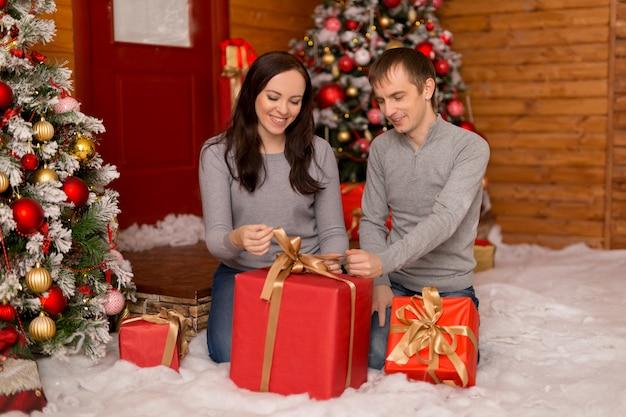 Schönes paar, eine junge familie in erwartung der frohen weihnachten öffnet geschenke.