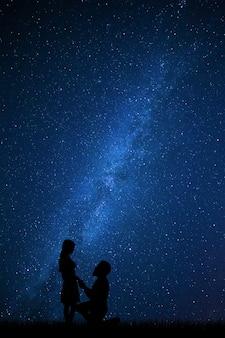 Schönes paar erklären liebe zueinander, freund blick auf mädchen, sterne am nachthimmel
