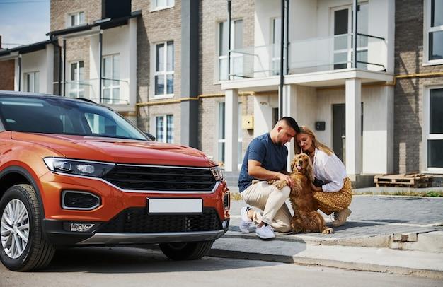 Schönes paar geht zusammen mit hund draußen in der nähe des autos spazieren.