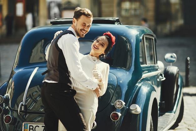 Schönes paar im 30er jahre stil gekleidet umarmungen auf der straße stehen vor einem alten auto