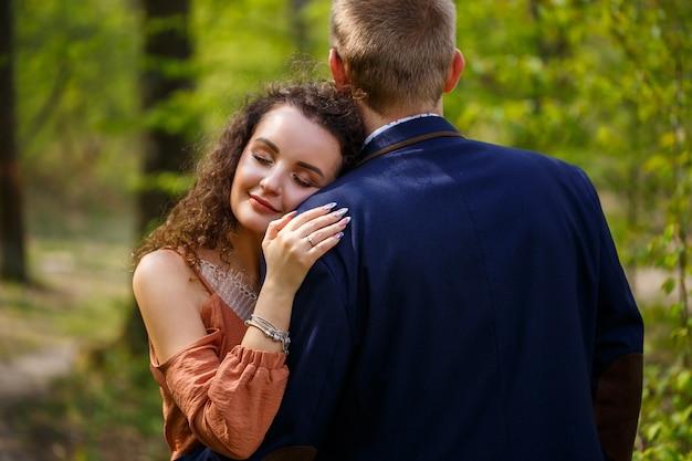 Schönes paar im wald. mädchen mit elegantem haarschnitt umarmt ihren mann im anzug. rustikales outdoor-details-fotografie-porträt. glückliche frau und freund