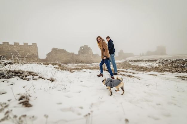 Schönes paar im winterfeld auf einem spaziergang mit dem hund. hund, der mit der schneebedeckten natur des besitzers im freien geht.