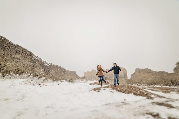 Schönes paar im winterfeld auf einem spaziergang mit dem hund.