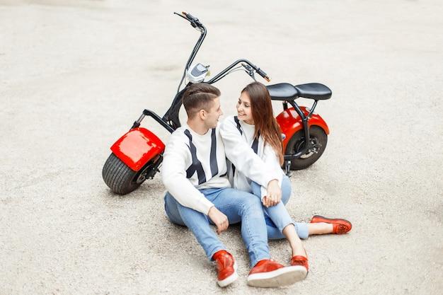 Schönes paar in modischer jeanskleidung ruht nahe einem roten elektrofahrrad auf weißem sand