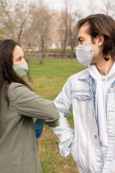 Schönes paar in stoffmasken, die ellbogen berühren, anstatt zu küssen, während sie sich im park treffen