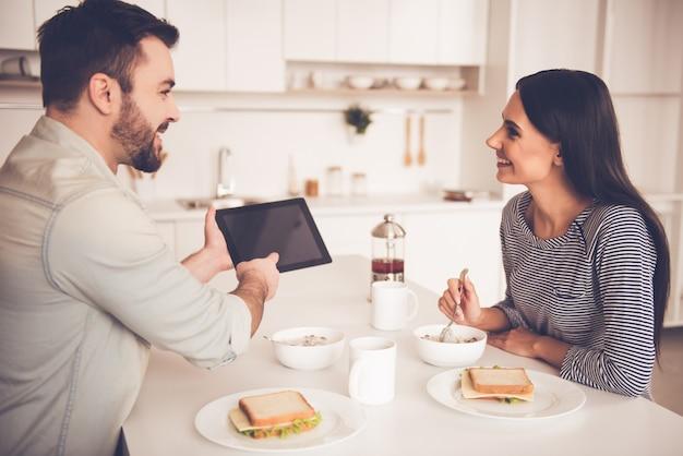 Schönes paar isst und benutzt eine digitale tablette
