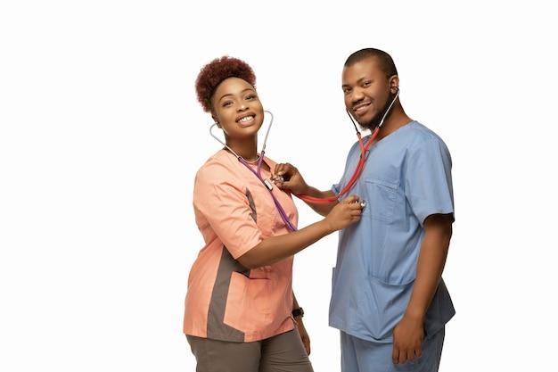 Schönes paar junger afroamerikanischer ärzte mit stethoskopen lächelnd isoliert auf weiß