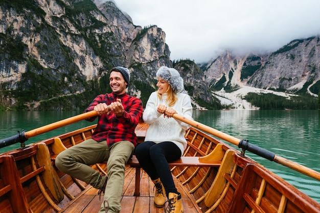 Schönes paar junger erwachsener, die einen alpensee bei braies italien besuchen