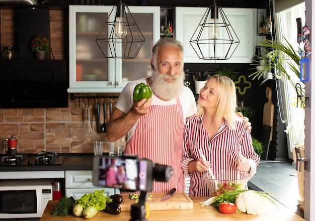 Schönes paar liebhaber blogger live-kochen in der küche für die arbeit von zu hause aus. covid-19. selektiver fokus.