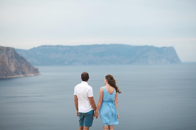 Schönes paar mann und frau, die zurück auf der klippe des berges stehen und den ozean betrachten.
