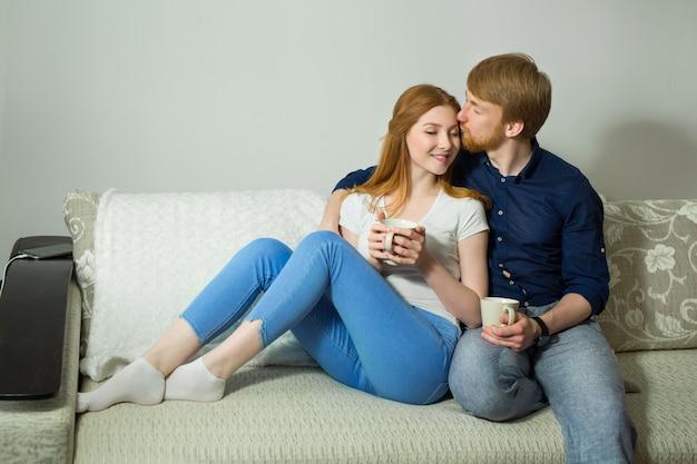 Schönes paar mann und frau sitzen auf dem sofa zu hause Premium Fotos